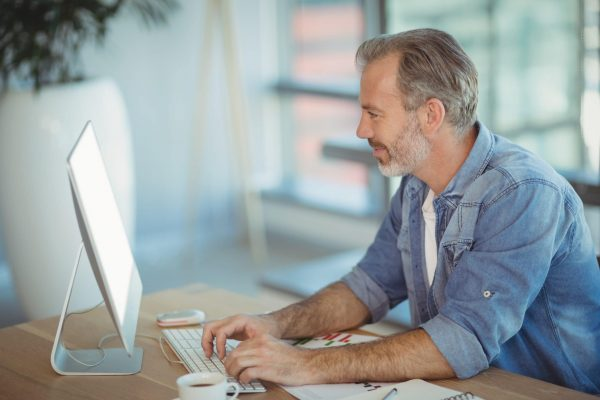 Male executive sitting at desk and working on personal computer in office
